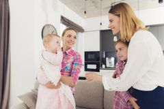 The babysitter meets the mother of the children, holding the baby in her arms. The older girl hugs Mom. Royalty Free Stock Image