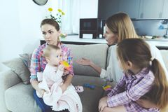 Babysitter and Mother Arguing and Holding Kids. Young Caucasian Angry Woman Holding Girl on Knees Sitting on Couch in Living Room and Has Arguing with Nanny stock photography