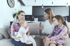 Babysitter and Mother Arguing and Holding Kids. Young Caucasian Angry Woman Holding Girl on Knees Sitting on Couch in Living Room and Has Conflict with Nanny royalty free stock images