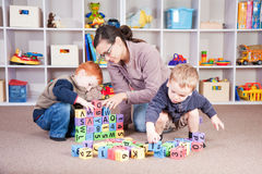 Babysitter playing kids block game with children. Babysitter playing game with children royalty free stock image