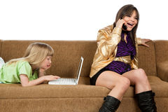 Babysitter talking on phone and young girl using Royalty Free Stock Images