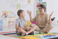 Babysitter and young boy. Sitting on a floor and talking royalty free stock photography