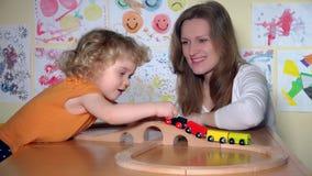 Babysitteren och nyfiken litet barnflickalek med träleksaken utbildar i dagis stock video