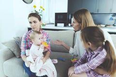 Babysittergespräch mit der Mutter von Kindern Sie hält das Baby in ihren Armen Die Mutter von Kindern schilt die Krankenschwester stockbilder