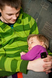 Babysitting. Cute family scene - teenage brother holding a baby sister while she sleeps. Babysitting concept Stock Photography