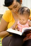 Babysitting mother read book to baby. Portrait of mother babysitting curious baby girl during readings outdoor stock photos