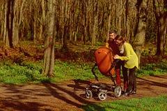Babysitting service Den uppsökte mannen och nätta kvinnan som babysitting med, behandla som ett barn pramen i vår parkerar Barnav royaltyfri bild