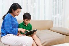 Babysitting. Young Vietnamese nurse babysitting with little child royalty free stock image