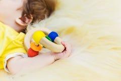 Babyslaap in de handen die een stuk speelgoed houden Stock Foto's