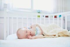 Babyslaap in mede-dwarsbalkvoederbak in bijlage aan het bed van ouders stock fotografie