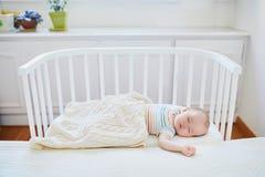 Babyslaap in mede-dwarsbalkvoederbak in bijlage aan het bed van ouders royalty-vrije stock afbeelding