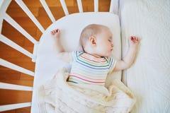 Babyslaap in mede-dwarsbalkvoederbak in bijlage aan het bed van ouders royalty-vrije stock foto