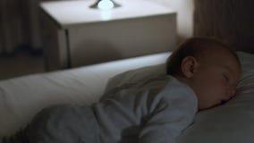Babyslaap in zijn bed bij nacht Stock Afbeelding