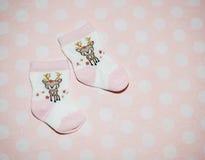 Babysocken auf rosa Hintergrund Stockbilder