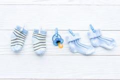 Babysocken auf Seil am hölzernen Hintergrund stockbilder