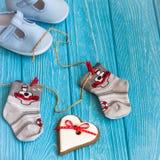 Babysocken auf Wäscheleine, Lebkuchenherzen und blauen Schuhen Stockfoto