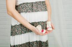Babysocken in den Händen der schwangeren Frau Stockfotografie