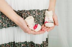 Babysocken in den Händen der schwangeren Frau Stockbild