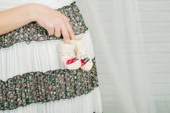 Babysocken in den Händen der schwangeren Frau Stockfotos