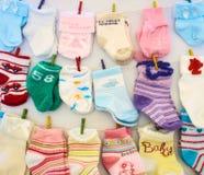 Babysocken und -handschuhe, die an den Linien mit Miniaturkleiderhaken hängen stockfotografie