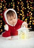 Babyspel met kaarslantaarn in Kerstmisdecoratie, gekleed als Kerstman, boke lichten op donkere achtergrond, het concept van de de Stock Afbeelding