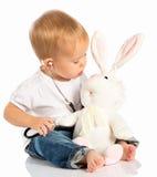 Babyspelen in artsenstuk speelgoed konijntjeskonijn en stethoscoop Royalty-vrije Stock Fotografie