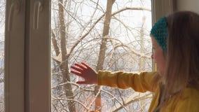 Babyspelen die op de vensterbank op de achtergrond van snow-covered bomen zitten stock footage