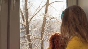 Babyspelen die op de vensterbank op de achtergrond van snow-covered bomen zitten stock videobeelden