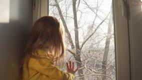 Babyspelen die op de vensterbank op de achtergrond van snow-covered bomen zitten stock video