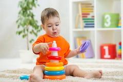 Babyspelen die op vloer zitten Onderwijsspeelgoed voor kleuterschool en kleuterschoolkind Weinig jongen bouwt piramidespeelgoed b stock afbeeldingen