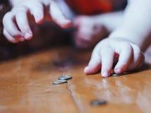 Babyspelen met muntstukken op vloer stock afbeelding