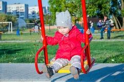 Babytochter des kleinen Mädchens in einer roten Jacke und in einem Hut auf dem Spielplatz, der auf ein Schwingen spielt und fährt Stockbild