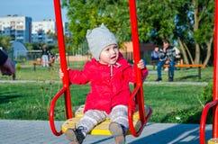 Babytochter des kleinen Mädchens in einer roten Jacke und in einem Hut auf dem Spielplatz, der auf ein Schwingen spielt und fährt Stockfotos