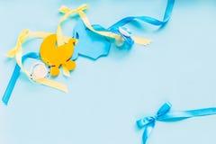 babytoebehoren op blauwe achtergrond, zoals soother, uitsteeksel, houten kleren, houten kleine baby stoller Stock Foto