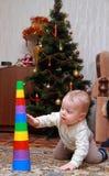 Babyversuch, zum der bunten Pyramide herunterzuziehen Lizenzfreies Stockbild