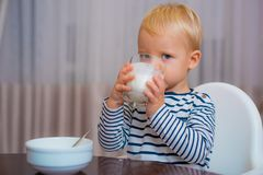 Babyvoeding Eet gezond Peuter die snack hebben Gezonde voeding Drink melk Het glas van de kindgreep melk Jong geitje leuke jongen stock fotografie
