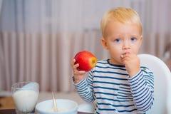 Babyvoeding Eet gezond Peuter die snack hebben thuis Het kind eet havermoutpap Blauwe ogen van de jong geitje zitten de leuke jon royalty-vrije stock fotografie
