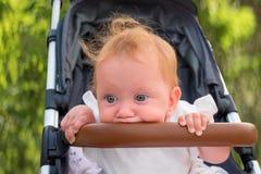 Babyvoertuigen Het zitten en het wachten op moeder Het leuke babymeisje wordt bored Jong geitje` s handen die bumper, familieconc stock fotografie