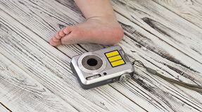 Babyvoet en digitale camera, witte houten achtergrond, close-up royalty-vrije stock afbeeldingen