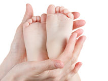 Babyvoeten in de handen van de moeder op wit worden geïsoleerd dat stock afbeeldingen