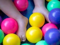 Babyvoeten met kleurrijke ballen stock foto