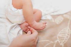 Babyvoeten in moeders mooie handen tot een kom worden gevormd met zachte nadruk op babie` s voet die stock fotografie