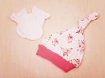 Babywaren Kind-` s Kleidung, Hut mit Blumen und weiße Handschuhe auf dem Hintergrund der ändernden Tabelle Lizenzfreie Stockbilder