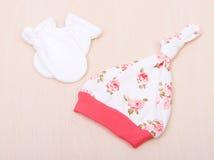 Babywaren Kind-` s Kleidung, Hut mit Blumen und weiße Handschuhe auf dem Hintergrund der ändernden Tabelle Lizenzfreies Stockbild