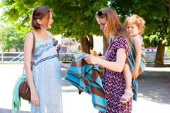 Babywearing-Mutter zeigt schwangerer Dame Riemen stockfotografie