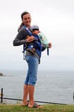 Babywearing. Young mother wearing happy baby boy Royalty Free Stock Photos