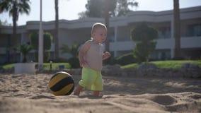 Babyweg nahe dem Ball, das auf dem Strand liegen stock video