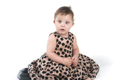 Babyzitting op de vloer in een mooie kleding Royalty-vrije Stock Foto's