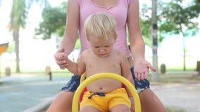 Babyzitting op het Gele Schommelen stock videobeelden