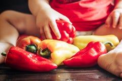 Babyzitting op lijst en het spelen met zoete groene paprika's Gezond voedsel voor kinderen Royalty-vrije Stock Foto's